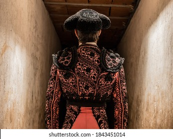 concentrated bullfighter waiting his turn in pink suit and cape.