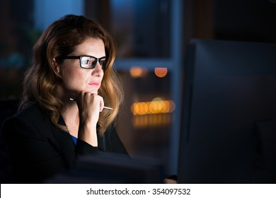 Concentrated business lady reading information on glowing screen on her computer