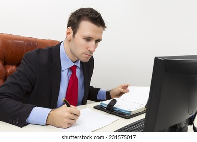 Concentrated business man analyzing data on computer display and filling a paper document.