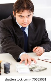 Concentrated business man  sitting at office desk and giving money packs