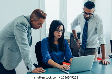 Concentrated business team discussing presentation together in office. Serious young multiethnic business expert preparing report and discussing strategy. Teamwork concept
