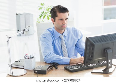 Concentrated businessman typing on the keyboard in the office