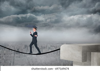 Concentrated businessman with umbrella walking against balcony overlooking city