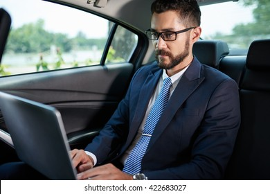 Concentrated businessman working on laptop when sitting on backseat of car