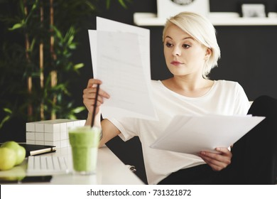 Concentrated businesswoman comparing documents at office