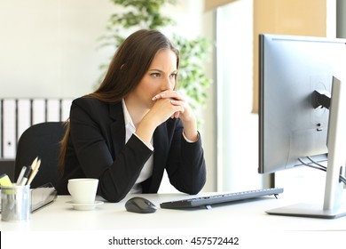 Concentrated businesswoman trying to solve a difficult assignment on line in a desktop computer at office