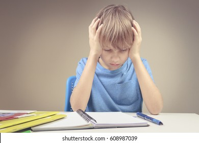 Concentrated child doing his homework at home. The boy sitting and looking in to books and notebooks. Education, school, learning difficulties concept