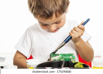A concentrated child painting a cardboard tube / Little boy painting