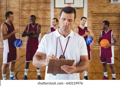 Concentrated coach writing on clipboard while team interacting in background