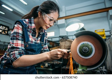 concentrated components factory female staff wearing safety goggles grinding steel product with abrasive disc and flying sparks in milling machine working area.