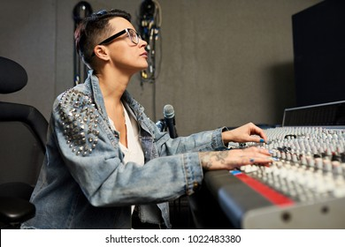Concentrated confident hipster female sound designer in eyeglasses using mixing desk while working in modern recording studio