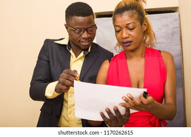 Concentrated couple of young colleagues working in modern offices. Two colleagues discussing their work, working with documents. Businesswoman pointing at a paper copy space