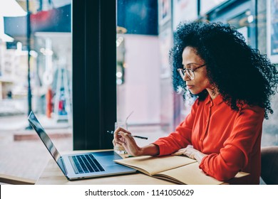 Concentrated dark skinned young woman in eyeglasses for vision correction reading information and preparing for studying seminar sitting at coffee table with laptop computer using wireless internet