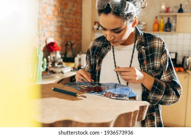 Concentrated designer making mosaic at her studio while working with glass