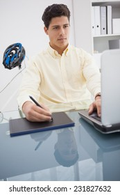 Concentrated designer using laptop and degitizer in his office