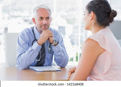 Concentrated doctor listening to patient in his office