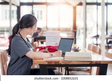 Concentrated doctor or nurse working on line with a laptop sitting in a desk in a consultation