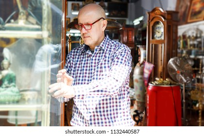 concentrated elderly man visiting shop of antique goods in search of interesting objects