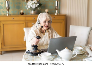 Concentrated Elderly Woman Actively Plays Video Games On The Laptop With The Help Of Joystick Among Teapot And Dishes