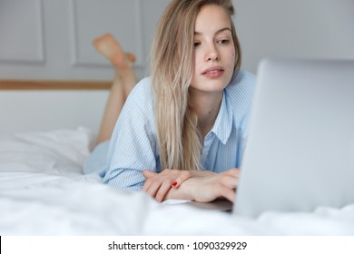 Concentrated European female bloger in striped casual night shirt, types article and surfes her blog before sleep, poses on comfortable bed against blurred bedroom interior, keeps feet in air.