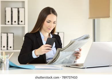 Concentrated executive reading a newspaper and using a smart phone at office