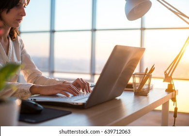 Concentrated female employee typing at workplace using computer. Side view portrait of a copywriter working on pc home.
