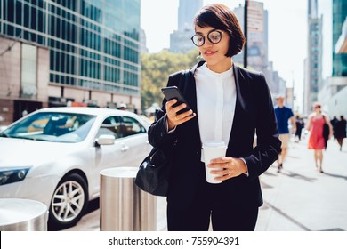 Concentrated female entrepreneur using application for calling taxi getting to work with morning coffee to go, prosperous businesswoman checking notification on smartphone strolling with takeaway
