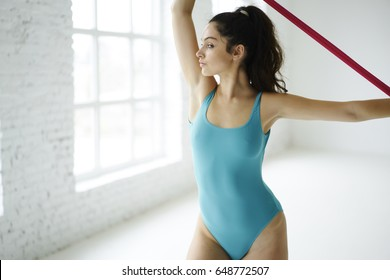 Concentrated female gymnastic girls satisfied with her perfect body shape having pilates workout using rubber band stretching muscles of upper body and hands training alone in white interior gym