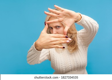 Concentrated female paparazzi with blond hair looking through fingers imagining frame to make good photos. Indoor studio shot isolated on blue background