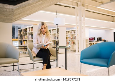 Concentrated female student sitting in library with modern interior and reading technology literature for making research of useful information, intelligent woman interested on book for leaders