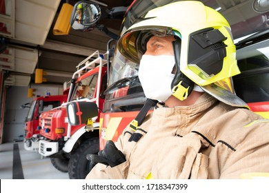 Concentrated firefighter equipped with a case intervention suit and mask to protect himself from the covid 19.