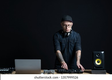 Concentrated and focused, professional DJ man making music in black modern and sound studio. He standing against black wall, using controller in style interior with copy empty space for text