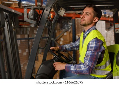 Concentrated forklift driver operating machine and holding hand on steering wheel. Professional driver in reflective waistcoat working with transportation of goods and packages in warehouse.