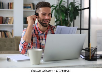 Concentrated freelancer businessman using laptop for video conferance, working remotely online at home. Smiling friendly handsome young male call center operator manager