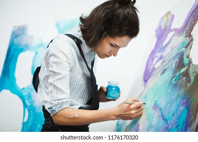 Concentrated girl focused on creative art-making process in art therapy
