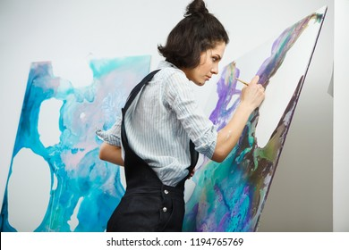 Concentrated girl focused on creative art-making process in art therapy concept. Form of psychotherapy that uses art media as its primary mode of communication