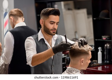 Concentrated hairdresser making professional and stylish haircut to client. Serious master using black comb and razor. Bearded barber wearing white classic shirt and grey vest.