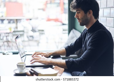 Concentrated handsome editor of popular online magazine typing text of new book review uploading it on web site after making skrip inspiring by literature using laptop computer and wifi connection