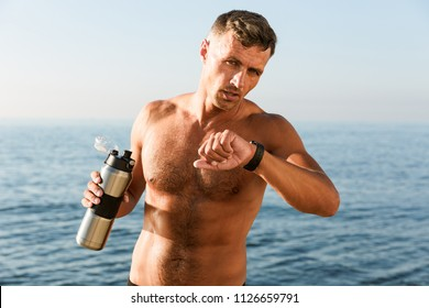 Concentrated handsome shirtless sportsman holding water bottle while standing at the beach and checking smartwatch