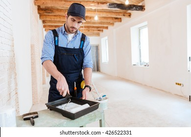 Concentrated handyman is preparing paint roller for work