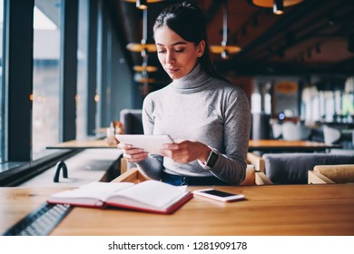 Concentrated hipster girl typing text messages and searching information about language cources via tablet, pondering woman chatting with friends online in social networks using new touchpad