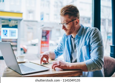 Concentrated hipster student reading information and checking data working at modern computer using wireless internet connection in coffee shop.Pensive young man preparing for exam at netbook