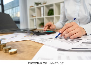 Concentrated intelligent clever lady in her formalwear shirt she sit behind desktop table with charts graph graphics in loft interior workplace check invoice write on blank by pen focus on hand