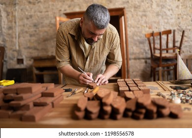 Concentrated joiner marks the wood blanks with a pencil. Wooden model of ship and the wood carpenter working.