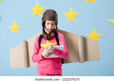 Concentrated kid with cardboard wings looking at digital tablet on blue starry background