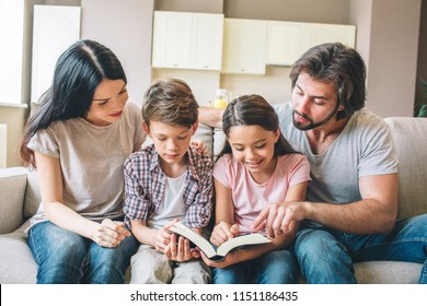 Concentrated kids are sitting on sofa with their parents and reading a book. Children hold it together. Guy is pointing on book.