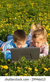 Concentrated kids using laptop on the spring flower field