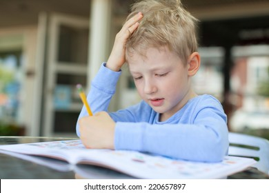 concentrated little boy doing homework