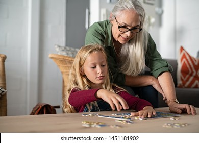 Concentrated little girl doing jigsaw puzzle with old grandmother at home. Cute little granddaughter playing puzzle at the table with senior granny. Smart child assembling pieces with mature woman.