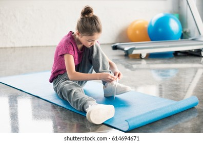 Concentrated little girl in sportswear sitting on mat and tying shoelace in gym